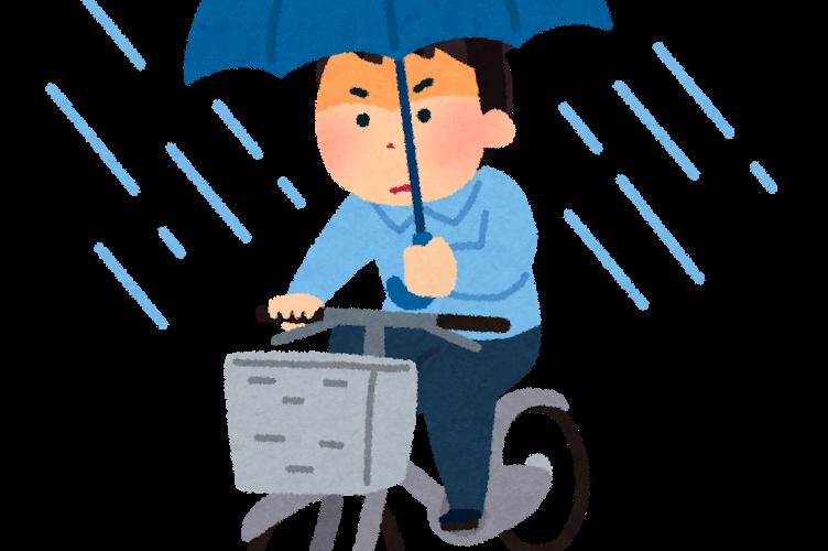 雨の中傘をさして自転車を漕ぐ人